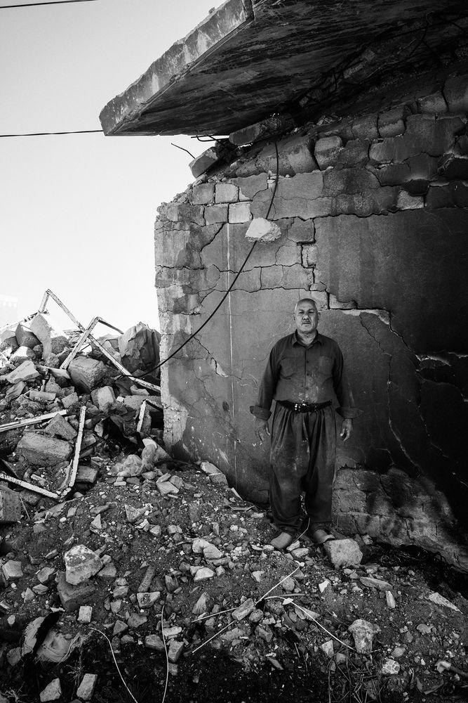 Mohsin Hairan Aswad, 60, a wealthy Yazidi Kurd from Bashiqa, stands in the remains of one of the seven homes that he owns. His homes were destroyed during the fighting to liberate the town from ISIS control in 2016. The next year, his son Faris, a local policeman in Mosul, was killed by an ISIS sniper. | Moises Saman—Magnum Photos for TIME
