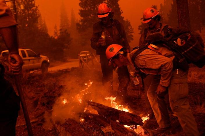 Firefighters improvise and spray water from their mouths to control a small spot fire while waiting for a hose line during the Windy Fire in the Sequoia National Forest near Johnsondale, California on September 22, 2021 (PATRICK T. FALLON/AFP via Getty Images)