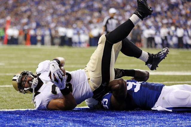 New Orleans Saints fullback Austin Johnson, top, goes over Indianapolis Colts outside linebacker Erik Walden for a touchdown during the first half of an NFL preseason football game in Indianapolis, Saturday, Aug. 23, 2014. (AP Photo/Sam Riche)