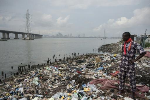 A man stands amid garbage near the sawmills area in Ebute Metta