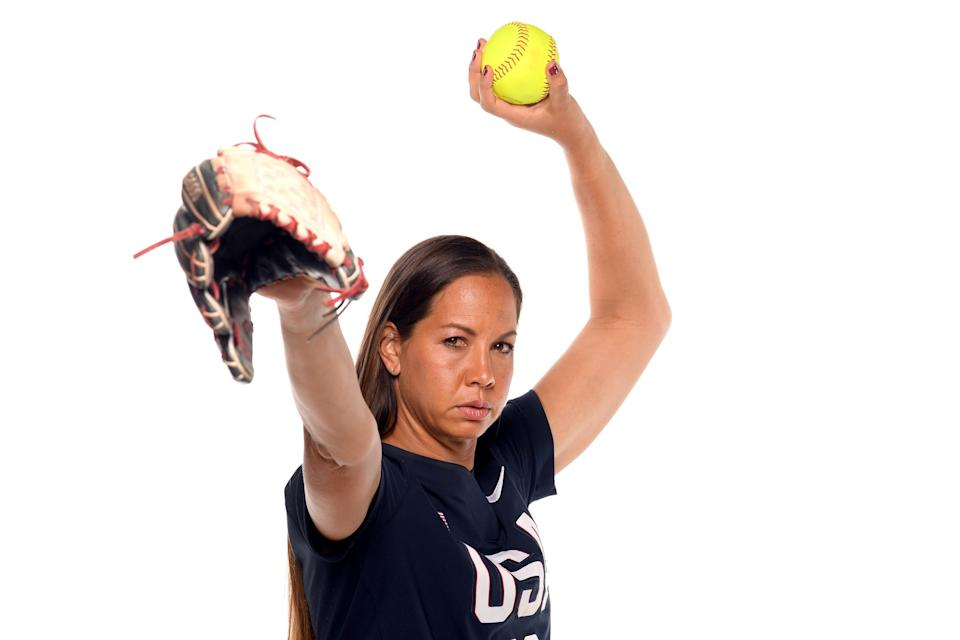 Cat Osterman poses with softball and glove while wearing USA shirt