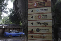 A sign that advertises the acceptance of cryptocurrencies at local businesses stands at one of the entrances of Zonte Beach in Tamanique, El Salvador, Wednesday, June 9, 2021. El Salvador's Legislative Assembly has approved legislation making the cryptocurrency Bitcoin legal tender in the country, the first nation to do so, just days after President Nayib Bukele made the proposal at a Bitcoin conference. (AP Photo/Salvador Melendez)