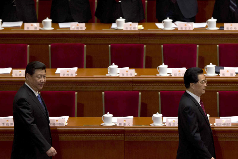 Communist Party chief Xi Jinping, left, walks behind Chinese President Hu Jintao at the opening session of the annual National People's Congress in Beijing's Great Hall of the People, China, Tuesday, March 5, 2013. China's government promised its people Tuesday deficit-fueled spending to fight deep-seated corruption, improve the despoiled environment and address other quality-of-life issues demanded by an increasingly vocal public looking for change. (AP Photo/Ng Han Guan)