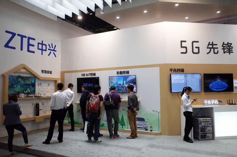 Visitors are seen at a booth of Chinese telecom equipment maker ZTE Corp at an expo in Beijing
