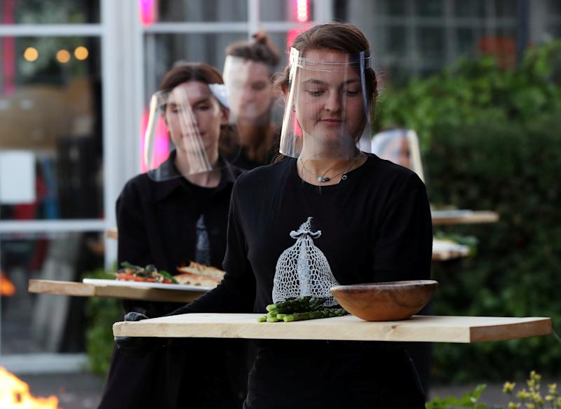 Servers are seen with protective gear carrying food at a restaurant in the Netherlands (Picture: Reuters)