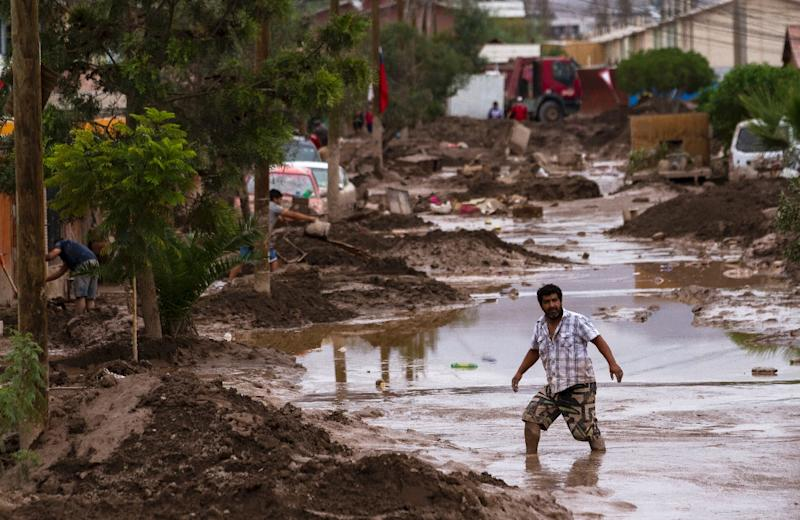 A man wades through a flooded street in Copiapo, after heavy rainfall caused the overflowing of the Copiapo river and the flooding of parts of the city in northern Chile, on March 30, 2015