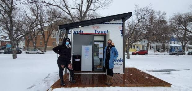 Brianne Kroener (left) is an organizer of the Cathedral Community Fridge, and Emily Norton (right) of Archangel Builders designed it and helped find people to build the fridge. (Samanda Brace/CBC News - image credit)
