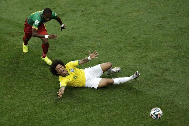 Brazil's Marcelo falls next to Cameroon's Eyong Enoh during the group A World Cup soccer match between Cameroon and Brazil at the Estadio Nacional in Brasilia, Brazil, Monday, June 23, 2014. (AP Photo/Christophe Ena)