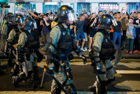 FILE PHOTO: Locals shout at riot police as they chase anti-government protesters down Nathan Road in Mong Kok in Hong Kong