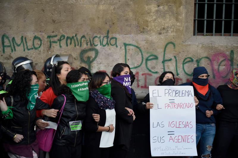 Demonstrators gather outside the National Palace, in Mexico City, on February 18, 2020, to protest gender violence. - Dozens of women protested Tuesday over the murder of a seven-year-old girl in the Mexican capital, a case that generated anger and outrage in a country used to violence. The murder of the minor shocked the country two days after hundreds of women protested in several cities in Mexico over the femicide of Ingrid Escamilla, a 25-year-old woman who was killed by her partner north of the Mexican capital. (Photo by ALFREDO ESTRELLA / AFP) (Photo by ALFREDO ESTRELLA/AFP via Getty Images)