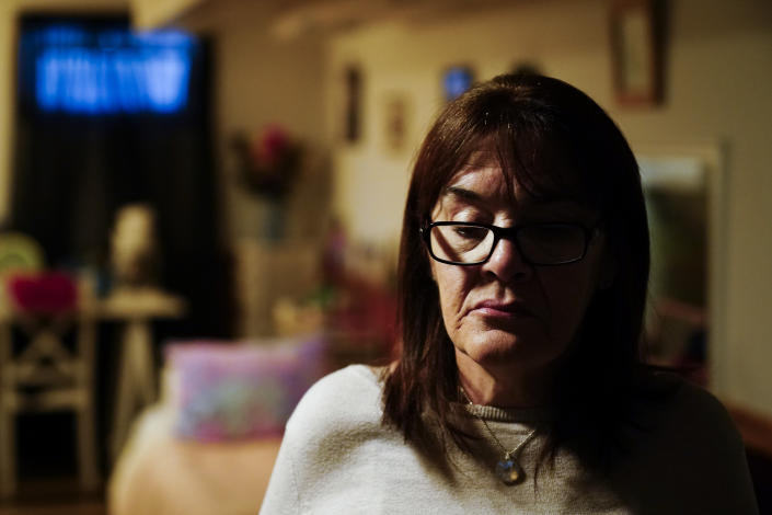 """Patti Burt walks in her sisters' home in Cherry Hill, N.J., Wednesday, March 10, 2021. When the first economic stimulus checks came through, Burt prayed the financial lifeline would ease some of the burdens her daughter, Ashley, was likely facing: """"I said, 'God, I hope they're happy.' I knew inside that Ashley was not happy, she was in pain."""" (AP Photo/Matt Rourke)"""