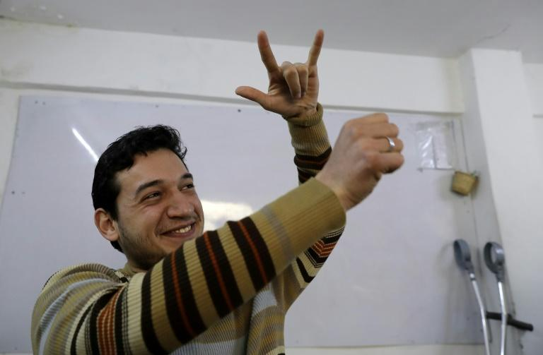 Ryad Hommos, a 21-year-old deaf Syrian, uses sign language during a class for deaf people at the EEMAA association, an NGO centre in Damascus' Midan district