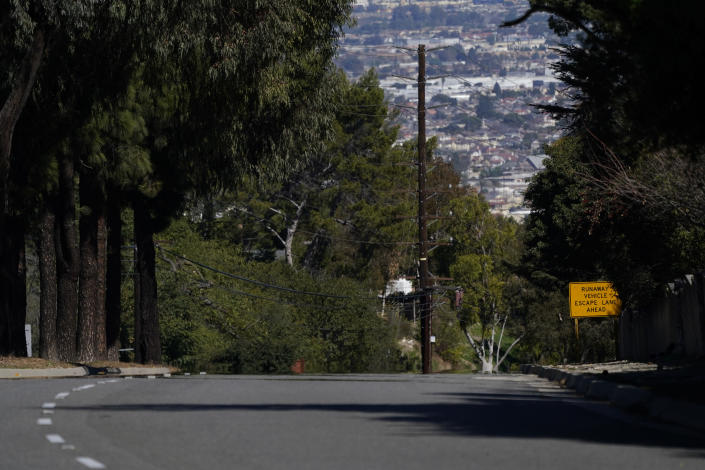 A runaway vehicle sign is posted on a section of Hawthorne Blvd near the site of a car crash involving golfer Tiger Woods, Tuesday, Feb. 23, 2021, in Rancho Palos Verdes, Calif., a suburb of Los Angeles. (AP Photo/Ashley Landis)