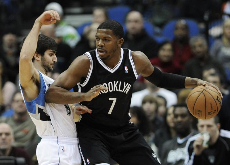 Minnesota Timberwolves' Ricky Rubio, left, of Spain, gets an elbow in the ribs by Brooklyn Nets' Joe Johnson in the first half of an NBA basketball game on Wednesday, Jan. 23, 2013, in Minneapolis. Johnson and teammate Deron Williams each scored 18 points in the Nets' 91-83 win. (AP Photo/Jim Mone)