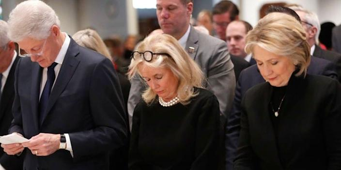Rep. Debbie Dingell bows her head with former President Bill Clinton and former Secretary of State Hillary Clinton during funeral services for her husband, former Rep. John Dingell.