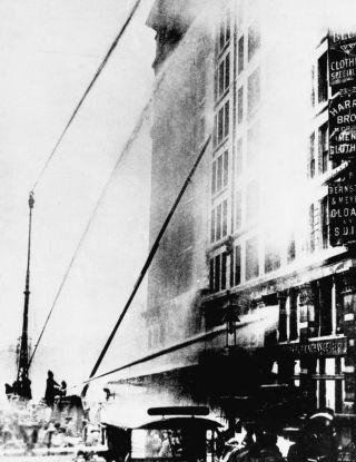 Firefighters work to extinguish the flames engulfing the top floors of the Triangle Shirtwaist Factory