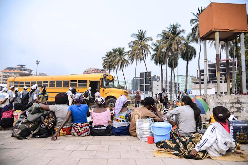 Angolans living in the Democratic Republic of Congo wait with bags at the train station in Kinshasa on August 19, 2014 as tens of thousands prepare to return home (AFP Photo/Junior D. Kannah)