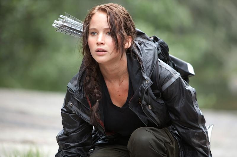 "In this image provided by Lionsgate, Jennifer Lawrence portrays Katniss Everdeen in a scene from ""The Hunger Games."" ""Bridesmaids"" and ""The Hunger Games"" are battling for the most buckets of golden popcorn at the MTV Movie Awards. The raunchy comedy and survival saga are the top nominees at Sunday's 21st annual extravaganza with eight nods apiece. (AP Photo/Lionsgate, Murray Close)"