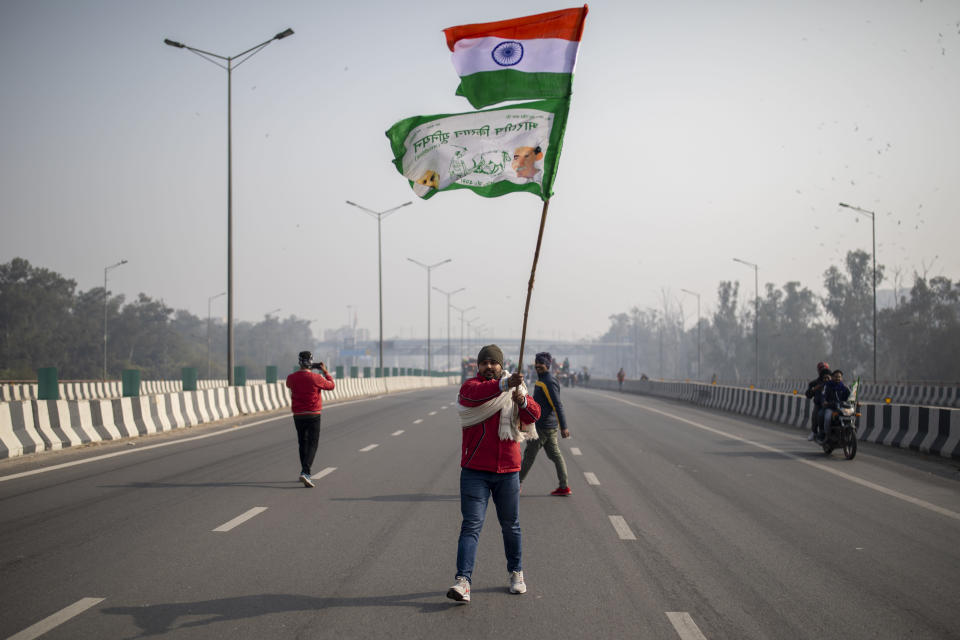 A protesting farmer waves an Indian flag and a farmer union flag as he marches with others to the capital breaking police barricades during India's Republic Day celebrations in New Delhi, India, Tuesday, Jan. 26, 2021. Tens of thousands of farmers drove a convoy of tractors into the Indian capital as the nation celebrated Republic Day on Tuesday in the backdrop of agricultural protests that have grown into a rebellion and rattled the government. (AP Photo/Altaf Qadri)