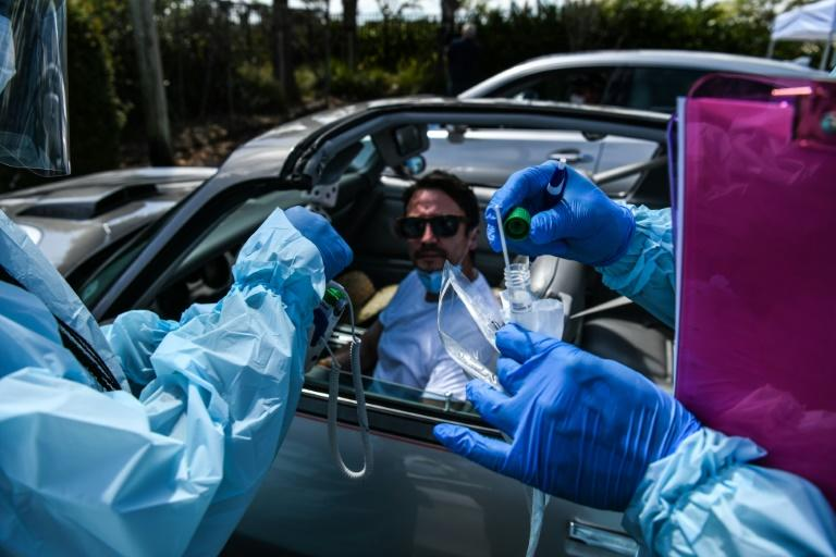 Health workers administer a test for coronavirus at a drive-through facility in West Palm Beach, Florida