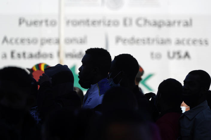 Asylum seekers waiting in Mexico stand in line at the border to receive news of policy changes, Friday, Feb. 19, 2021, in Tijuana, Mexico. After waiting months and sometimes years in Mexico, people seeking asylum in the United States are being allowed into the country starting Friday as they wait for courts to decide on their cases, unwinding one of the Trump administration's signature immigration policies that President Joe Biden vowed to end. (AP Photo/Gregory Bull)