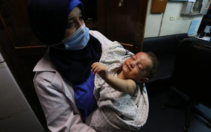 A nurse holds a baby, who was pulled alive from under the rubble while seven other family members perished, at Al-Shifa Hospital, Gaza, - APAImages/Shutterstock