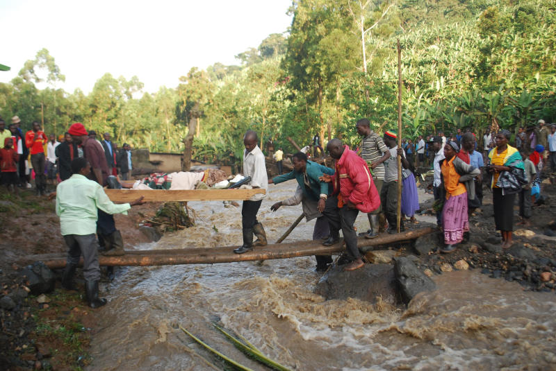 Residence carry an injured person over a river filled with mud in Bududa District, Uganda, Friday, Oct. 12, 2018. At least 30 people died in mudslides triggered by torrential rains in a mountainous area of eastern Uganda that is prone to such disasters, a Red Cross official said Friday. More victims were likely to be discovered when rescue teams access all the affected areas in the foothills of Mount Elgon, said Red Cross spokeswoman Irene Nakasiita. (AP Photo/ Ronald Kabuubi)