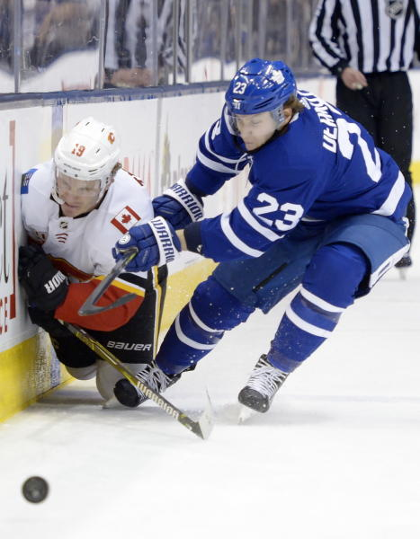 Toronto Maple Leafs defenseman Travis Dermott (23) checks Calgary Flames left wing Matthew Tkachuk (19) during the third period of an NHL hockey game Thursday, Jan. 16, 2020, in Toronto. (Nathan Denette/The Canadian Press via AP)