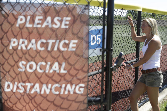 Kate Nunley watches as professional and college players workout at Grand Park, Friday, June 12, 2020, in Westfield, Ind. Proceeds from the event will go to Reviving Baseball in the Inner City of Indianapolis. (AP Photo/Darron Cummings)
