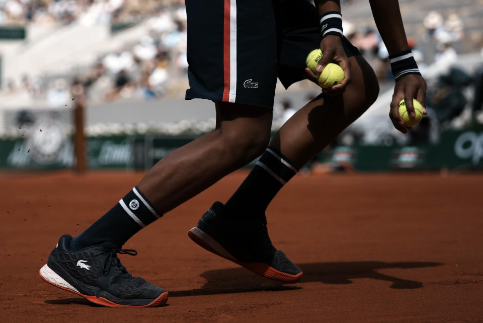 A ballboy collects the tennis balls on Philippe Chatrier court during Stefanos Tsitsipas of Greece playing against Spain's Pablo Carreno Busta fourth round match on day 8, of the French Open tennis tournament at Roland Garros in Paris, France, Sunday, June 6, 2021. (AP Photo/Thibault Camus)