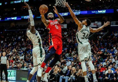 Dec 13, 2017; New Orleans, LA, USA; New Orleans Pelicans center DeMarcus Cousins (0) shoots between Milwaukee Bucks forward Giannis Antetokounmpo (34) and center Thon Maker (7) during the second half at the Smoothie King Center. The Pelicans defeated the Bucks 115-108. Derick E. Hingle-USA TODAY Sports