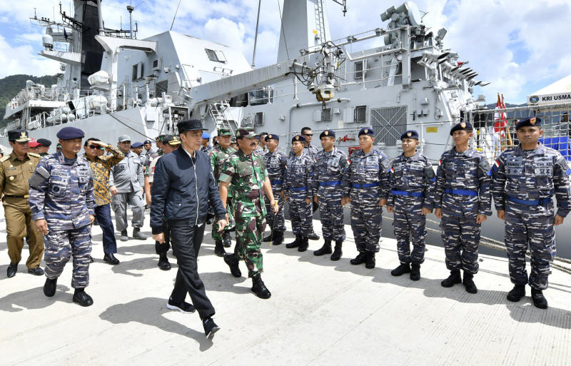 In this photo released Indonesian Presidential Office, Indonesian President Joko Widodo, center, inspect troops during his visit at Indonesian Navy ship KRI Usman Harun at Selat Lampa Port, Natuna Islands, Indonesia, Wednesday, Jan. 8, 2020. Indonesian President Joko Widodo on Wednesday visited the Natuna islands that overlap with China's expansive claim to the South China Sea amid heightened tensions over the waters after Beijing recently claimed it was their traditional fishing area. (Agus Soeparto, Indonesian Presidential Office via AP)