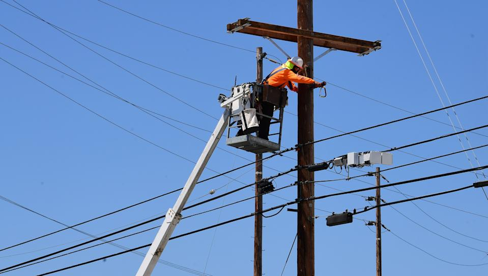 A man works on power lines in Los Angeles, California on May 4, 2020, amid the coronavirus pandemic. - California governor Gavin Newsom earlier today announced the gradual reopening of the state later this week as dismal US employment figures are expected with the release of figures Friday May 8 for April's US jobs report, as 30 million Americans filed for unemployment in the last six weeks. (Photo by Frederic J. BROWN / AFP) (Photo by FREDERIC J. BROWN/AFP via Getty Images)