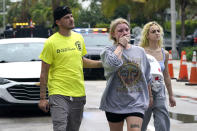 ADDS NAME OF HEVIA'S MOTHER AND THAT SHE DIED IN THE COLLAPSE - Ariana Hevia, of New Orleans, center, walks with Sean Wilt, left, on Friday, June 25, 2021, near the 12-story beachfront condo building that collapsed on Thursday in Surfside, Fla., north of Miami. Hevia's mother, Cassondra Billedeau-Stratton, lived in the building and is listed among those who died in the collapse. (AP Photo/Lynne Sladky)