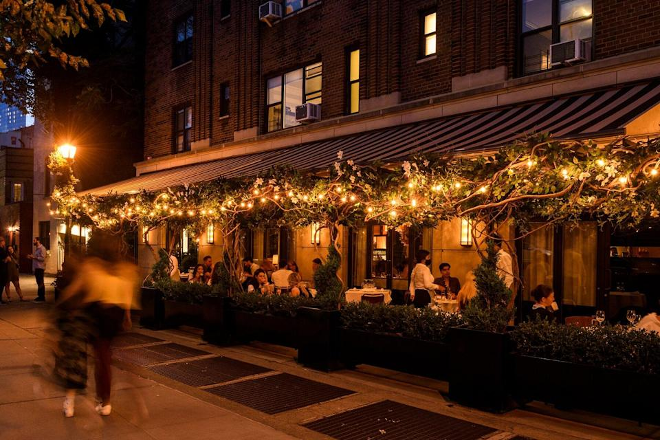 Evening view of whimsical patio lit by fairy lights at Hancock St