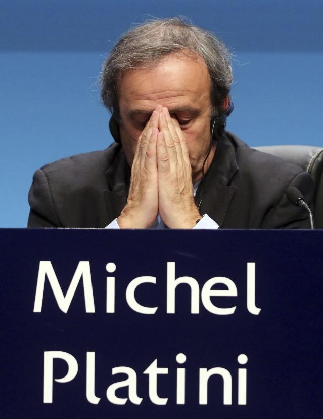FILE - In this Tuesday, March 24, 2015 file photo UEFA President Michel Platini covers his face during a news conference at the end of the 39th Ordinary UEFA Congress in Vienna, Austria. Former UEFA president Michel Platini has been arrested Tuesday June 18, 2019 over the awarding of the 2022 World Cup. (AP Photo/Ronald Zak, File)