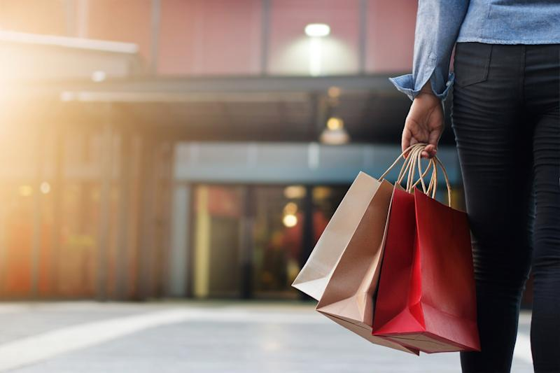 Shopper holding bags and walking toward mall entrance.