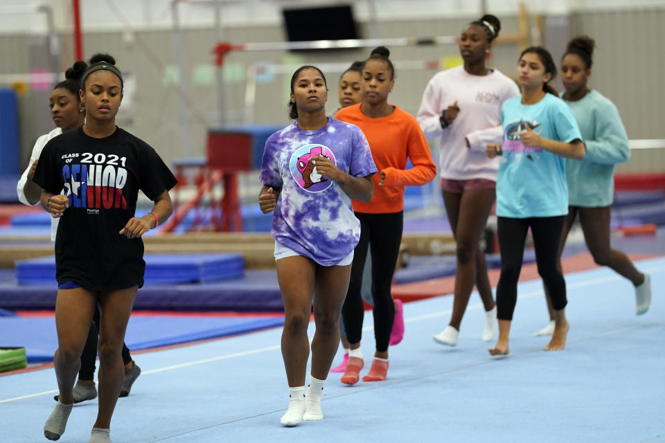 FILE - In this May 11, 2021, file photo, gymnast Jordan Chiles, center, trains in Spring, Texas. The 20-year-old Chiles will compete at the U.S. Championships this weekend hoping to build off a strong performance at the U.S. Classic, where she finished second to Olympic and world champion Simone Biles. (AP Photo/David J. Phillip, File)