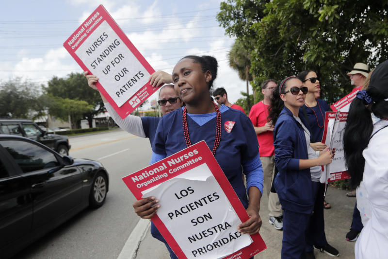 """Nurse Alexandra Rene carries a sign reading """"Patients are our Priority"""" during a one-day strike outside of Palmetto General Hospital, Friday, Sept. 20, 2019, in Hialeah, Fla. Registered nurses staged a one-day strike against Tenet Health hospitals in Florida, California and Arizona on Friday, demanding higher wages and better working conditions. (AP Photo/Lynne Sladky)"""