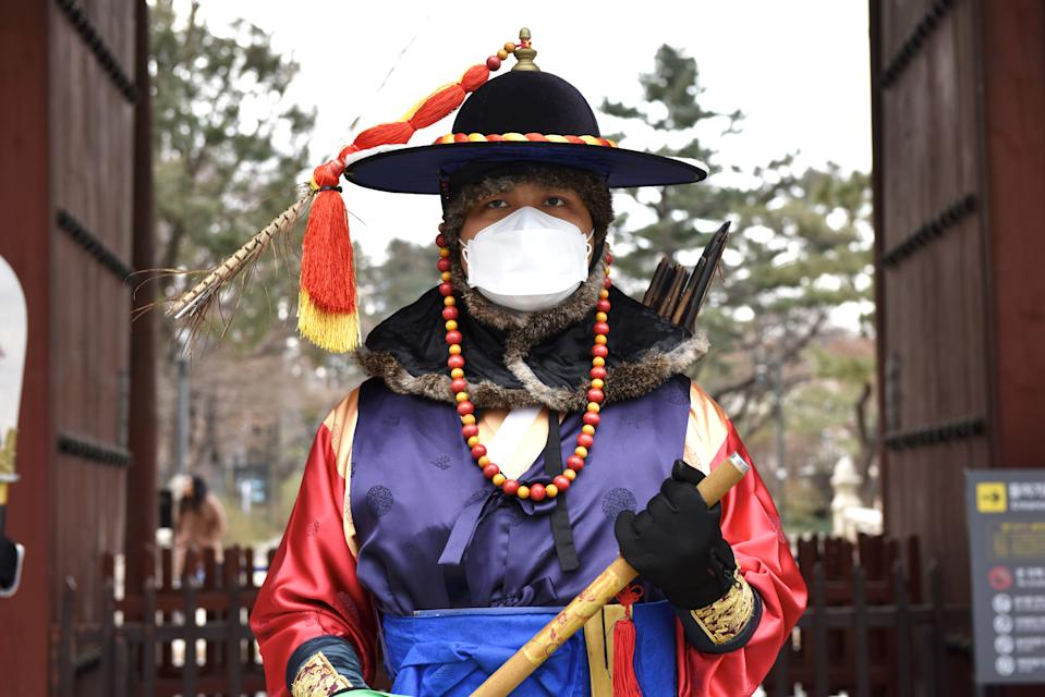 SEOUL, SOUTH KOREA - FEBRUARY 7, 2020: A royal guard in a medical mask by the Deoksugung Palace in central Seoul. The Chinese authorities registered an outbreak of the 2019-nCoV coronavirus in Wuhan in December 2019; as of February 7, 2020, the number of people infected with the new strain of coronavirus has risen over 30,000, the death toll is over 600. Stanislav Varivoda/TASS (Photo by Stanislav Varivoda\TASS via Getty Images)
