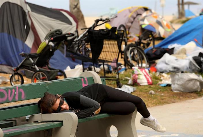 A woman sleeps on a bench against a backdrop of homeless encampments