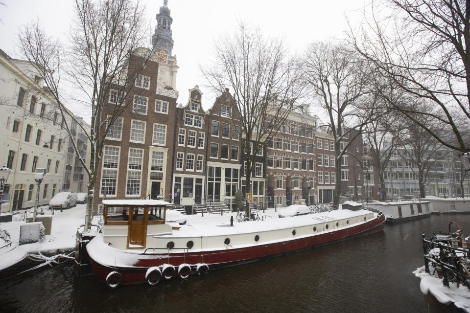 Snow covers a houseboat in Amsterdam, as snow and strong winds blanketed much of the Netherlands, Sunday, Feb. 7, 2021. (AP Photo/Peter Dejong)