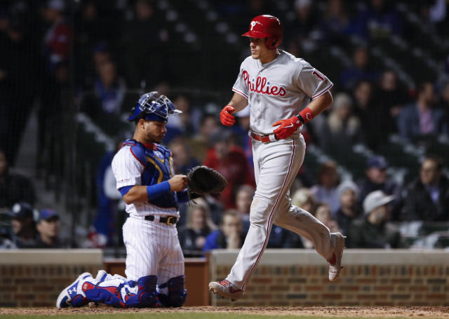 Philadelphia Phillies' J.T. Realmuto, right, crosses home plate after hitting a solo home run against the Chicago Cubs during the 10th inning of a baseball game, Monday, May 20, 2019, in Chicago. (AP Photo/Kamil Krzaczynski)
