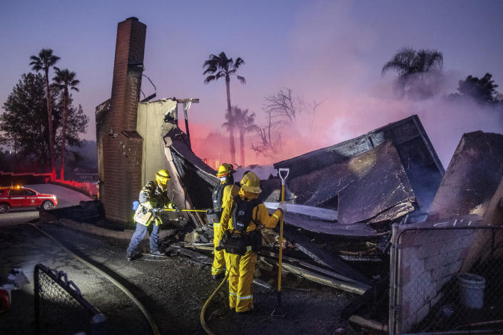 Firefighters mop up at a leveled home as the Hillside Fire burns in San Bernardino, Calif., on Thursday, Oct. 31, 2019. The blaze, which ignited during red flag fire danger warnings, destroyed multiple residences. (AP Photo/Noah Berger)