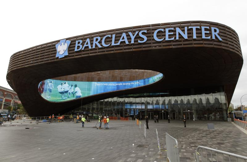 FILE - This Sept. 20, 2012 file photo shows workers sweeping the plaza in front of the main entrance to the Barclays Center in the Brooklyn borough of New York. A person familiar with the situation says the New York Islanders have struck a deal to move to Barclays Center as early as 2015. The person was not authorized to discuss the situation prior to an afternoon announcement, Wednesday, Oct. 24, 2012,  and spoke to The Associated Press on condition of anonymity. (AP Photo/Kathy Willens, File)
