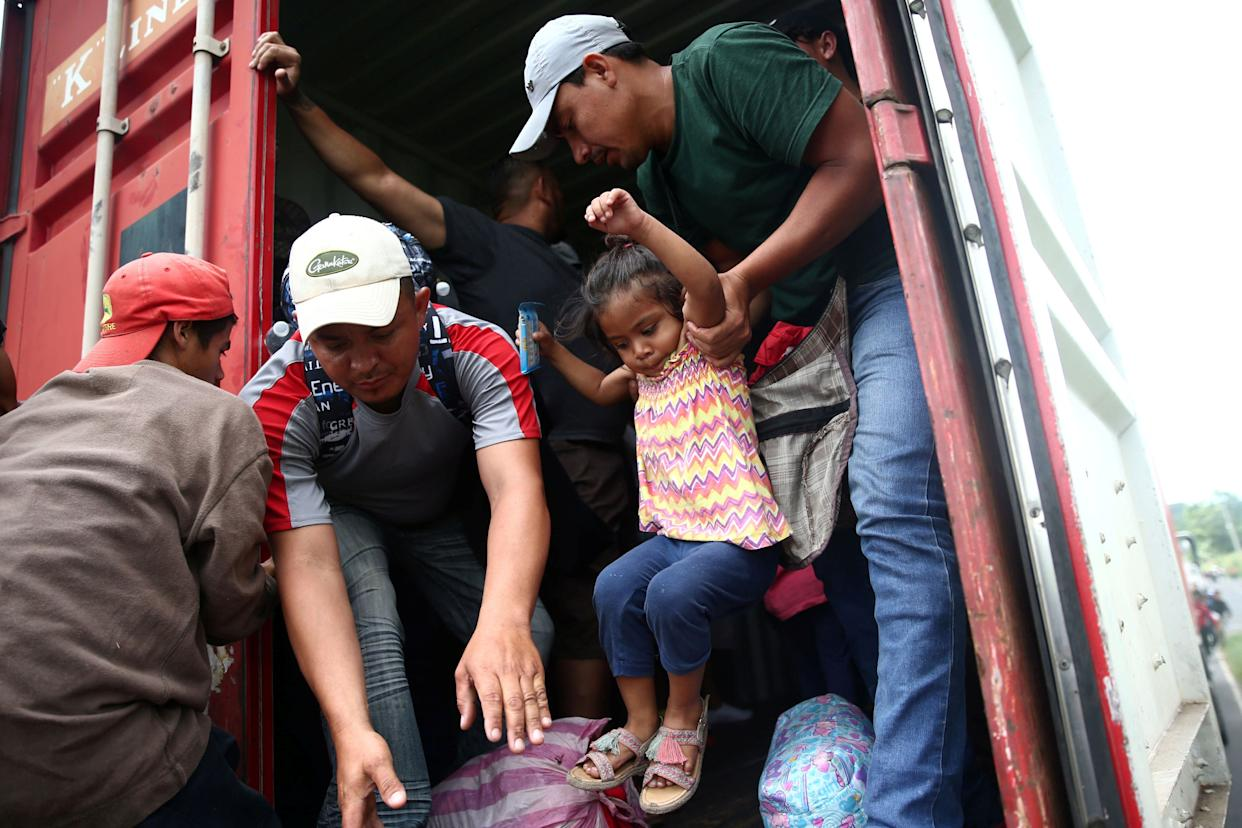 Migrants lift each other into the back of a truck.