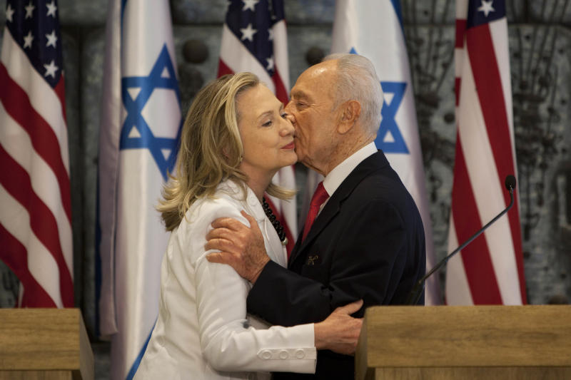 U.S. Secretary of State Hillary Rodham Clinton, left, and Israel's President Shimon Peres, hug after a joint statement at the President's residence in Jerusalem, Monday, July 16, 2012. Clinton met Peres for about an hour as part of what is perhaps her final visit to Israel as secretary of state, bringing a message of solidarity to the Jewish state after three-and-a-half years of only stunted progress toward a Palestinian peace deal. (AP Photo/Oded Balilty)