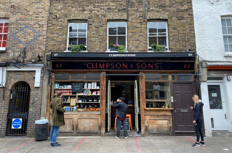 FILE PHOTO: People observe social distancing rules outside Climpson & Sons coffee shop in Hackney