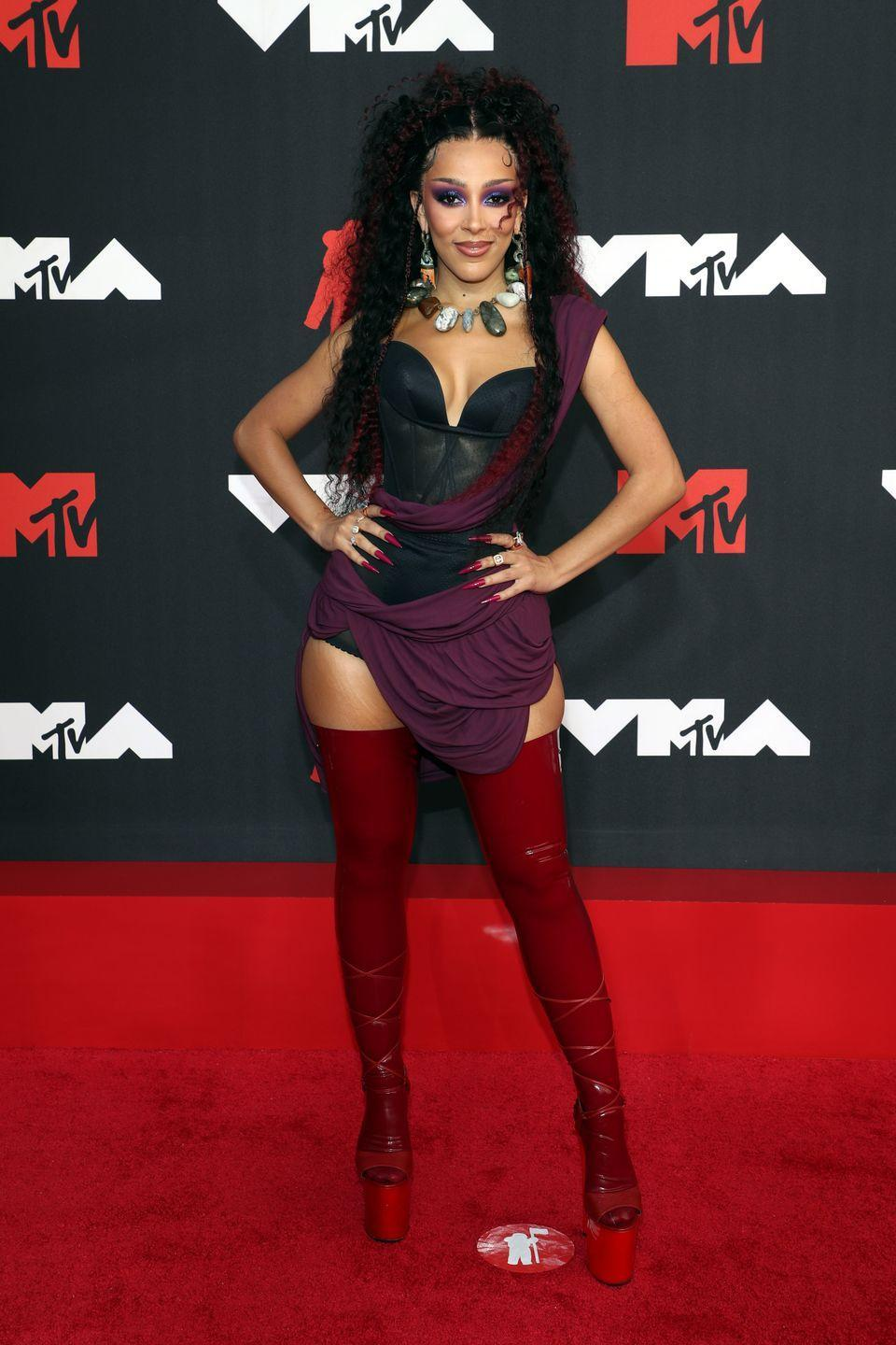 <p>Host Doja Cat slayed in a black and maroon bodysuit and statement red over-the-knee platform boots. She accessorized with a stone-beaded necklace and wore matching red hair streaks. </p>