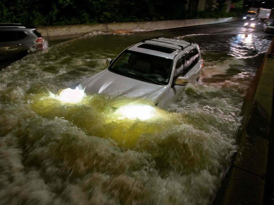 A motorist drives a car through a flooded expressway in Brooklyn, New York early on September 2, 2021 (AFP via Getty Images)